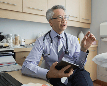 Asian doctor facing right speaking with tablet in hand.