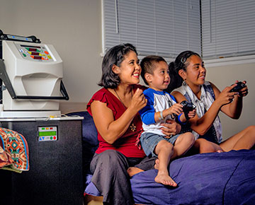 DaVita home dialysis patient at home watching her children play video games