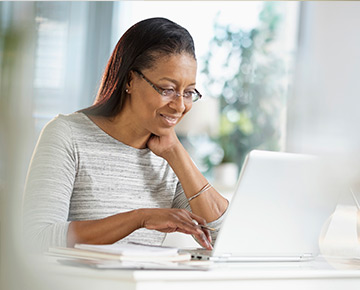 Woman sitting at desk looking at a laptop computer