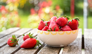 Bowl of strawberries sitting on a table